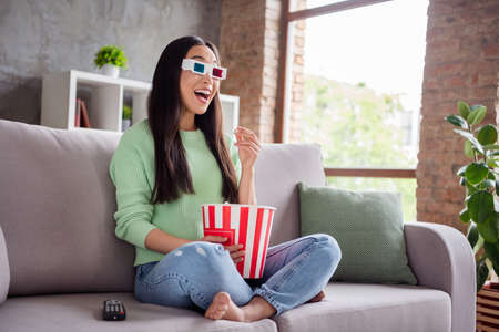 Full body profile side photo of astonished positive asian girl sit divan legs crossed barefoot watch 3d film glasses impressed effect eat pop corn box in house indoors