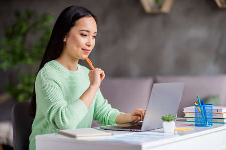 Photo of focused asian girl sit cozy desk work study remote prepare report hold pen copybook look laptop screen in house indoors