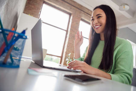 Low angle view profile side photo of asian positive education study blogger girl sit table use laptop greet coach seminar webinar waving hand in house indoors