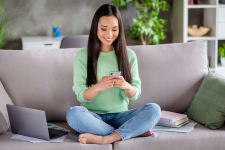 Full body photo of positive korean girl sit couch legs crossed folded use smartphone repost subscribe comment social media post in house indoors