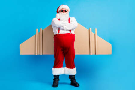 Full body photo of confident aviator white grey hair bearded santa claus cross hands have craft wings x-mas christmas gift dream delivery wear suspenders overall isolated blue color background