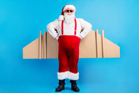 Full length photo of crazy overweight santa claus with big stomach have craft wings fly x-mas christmas party wear suspenders overall sunglass boots isolated blue color background