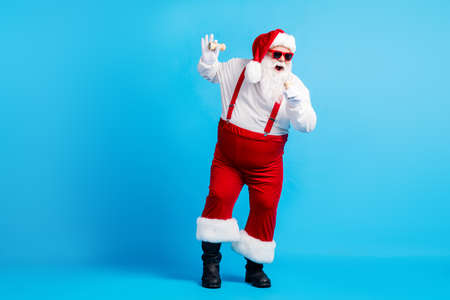 Full body photo of stylish crazy funky cool hipster santa claus with big abdomen sing x-mas christmas song pepper mic wear red suspenders overalls sunglass isolated blue color background