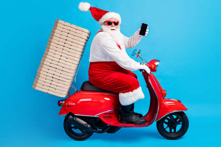 Full body profile side photo of white grey hair bearded santa claus drive motor bike travel x-mas christmas eve pile pizza wear red hat costume isolated over blue color background