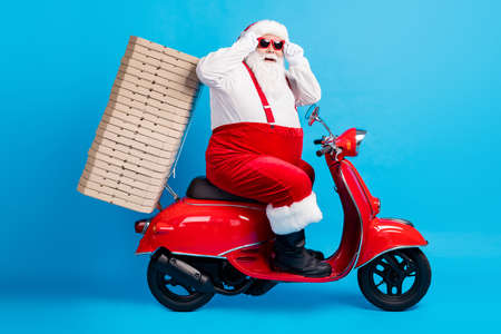 Full length profile side photo of stylish modern white grey hair bearded santa claus drive motor bike deliver x-mas christmas noel pizza stack wear red costume isolated blue color background Stock Photo