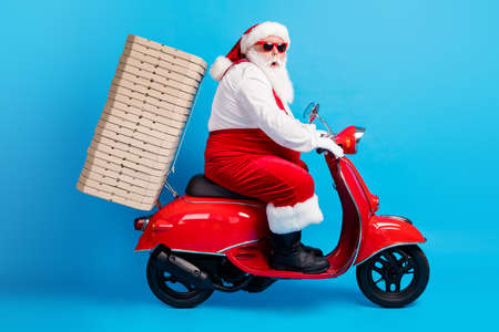 Full size profile side photo of stylish modern santa claus with big belly grey beard drive scooter deliver x-mas christmas pile stack pizza wear red costume isolated over blue color background