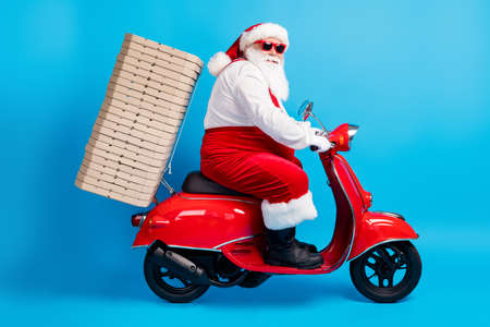 Full length profile side photo of stylish modern crazy white grey hair bearded santa claus drive motorbike deliver x-mas pile stack pizza wear suspenders overall isolated blue color background
