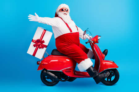 Full length profile photo of grandfather grey beard ride motorcycle deliver present raise hand wear santa x-mas costume suspenders sunglass white shirt cap isolated blue color background