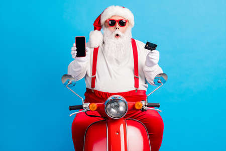 Photo of grandfather grey beard drive retro moped hold debit card phone screen empty space wear santa x-mas costume suspenders sunglass white shirt hat isolated blue color background