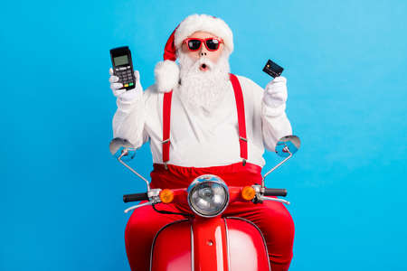 Photo of grandfather grey beard ride retro moped hold demonstrate debit card terminal wear santa claus x-mas costume suspenders sunglass white shirt cap isolated blue color background