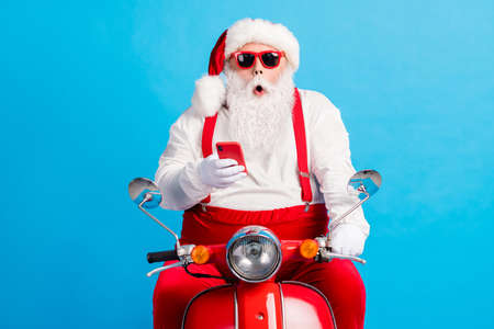 Photo of grandfather grey beard ride retro moped open mouth hold telephone wear santa claus x-mas costume suspenders sunglass white shirt headwear gloves isolated blue color background