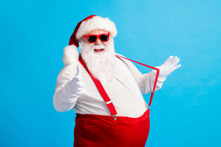 Photo of modern style santa claus with big abdomen pull suspender point index finger gloves x-mas christmas noel ads wear sunglass cap overalls pants isolated blue color background