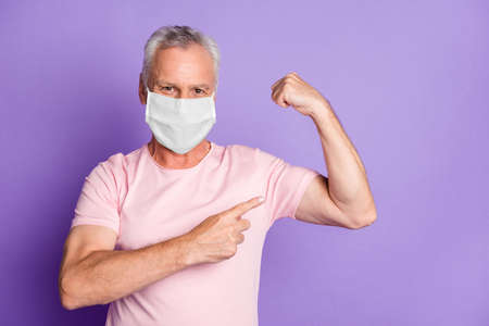 Photo of old man flex muscles point finger wear white face mask isolated purple color background