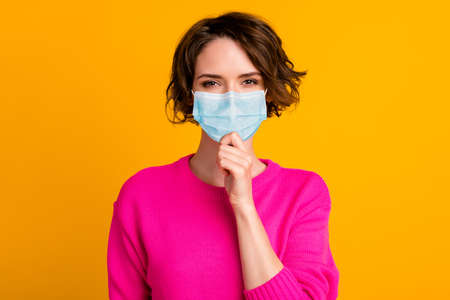 Portrait of minded girl touch chin finger wear blue face mask isolated over vivid yellow color background