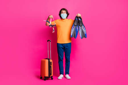 Full length photo of guy luggage show mask flips wear medical mask t-shirt jeans isolated pink color background Imagens