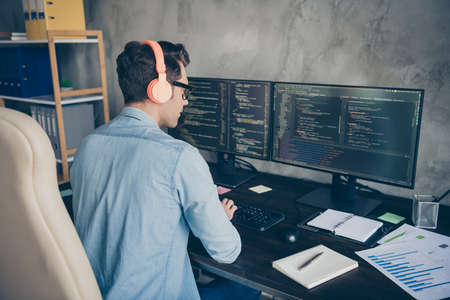 Rear back behind view portrait of his he nice skilled busy geek guy typing php language C plus editing sql database source at modern industrial interior style concrete wall work place station