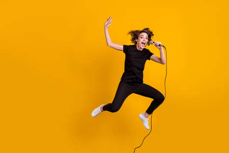 Full length body size view of pretty cheerful funky skinny girl artist jumping singing rock isolated bright yellow color background Stock Photo