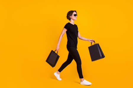 Full length body size profile side view of nice cool cheerful girl going carrying bringing parcel isolated bright yellow color background