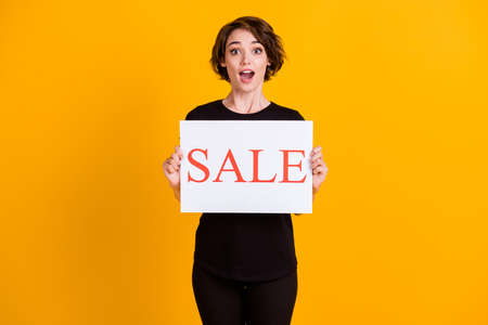 Portrait of attractive amazed cheerful girl holding in hand paper poster sale word isolated on bright yellow color background