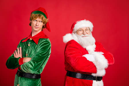 Profile photo of two men crossed arms santa claus smile elf frown wear x-mas costume coat headwear isolated red color background