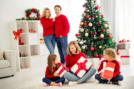Photo of full big family five people meeting three little kids hold boxes ribbon bow guess present parents spectate near x-mas tree wear red jumper jeans in home living room indoors