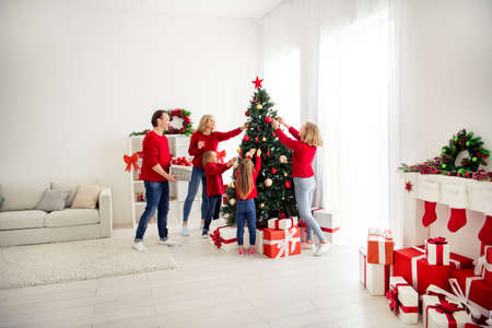 Photo of full big family five people meeting three little kids decorate x-mas tree dad help bring basket baubles garland wear red jumper jeans in home living room many gift box indoors