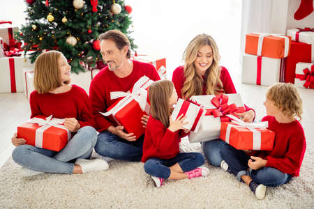 Photo of full family five people gathering three small kids sit carpet exchange big boxes present wear red jumper jeans in living room x-mas tree garland many gifts indoors Stock Photo
