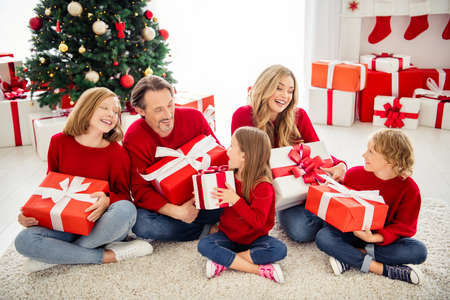 Photo of full big family five people meeting three little kids sit carpet hold exchange presents girl wear red jumper jeans in living room x-mas tree garland many presents indoors