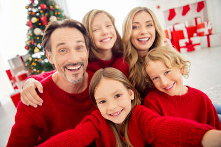 Closeup selfie photo of full big family five people meeting three little kids embrace toothy beaming smiling wear red jumper in living room x-mas tree garland gift boxes indoors