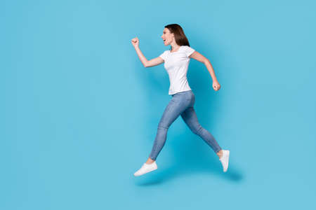 Full length body size profile side view of her she nice attractive purposeful slim fit skinny cheerful girl jumping running marathon motion isolated bright vivid shine vibrant blue color background