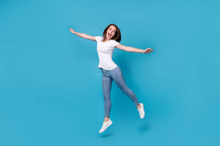 Full length body size view of her she attractive pretty funky skinny overjoyed cheerful cheery girl jumping having fun wear comfort clothes isolated bright vivid shine vibrant blue color background