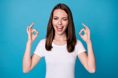 Portrait of excited girl show okay symbol recommend suggest select adverts promo wink blink wear good look outfit isolated over blue color background
