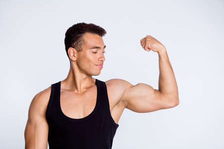 Close-up portrait of his he nice attractive sportive successful muscular cheery guy demonstrating looking at powerful muscles goal protein diet isolated over light gray pastel color background