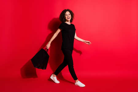 Full length photo of sweet adorable wavy lady dressed casual black outfit walking holding shopping bags isolated red color background