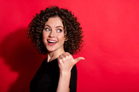 Photo of adorable cute wavy lady dressed casual black outfit looking pointing back one finger empty space isolated red color background Banque d'images