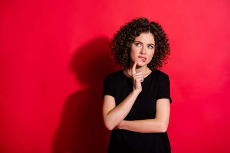 Photo of serious adorable curly woman wear casual black outfit finger chin looking empty space isolated red color background
