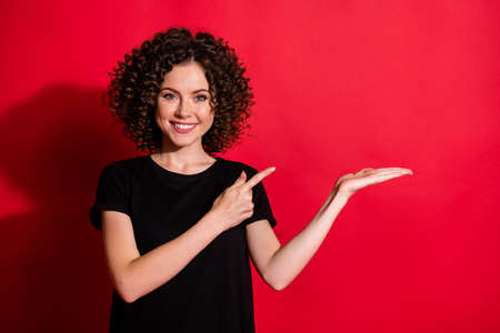 Portrait of pretty cheerful content wavy-haired girl holding in palm demonstrating copy space advert isolated over bright red color background