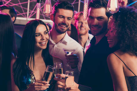 Photo portrait of attractive people drinking together champagne at nightclub speaking holding tasty beverage