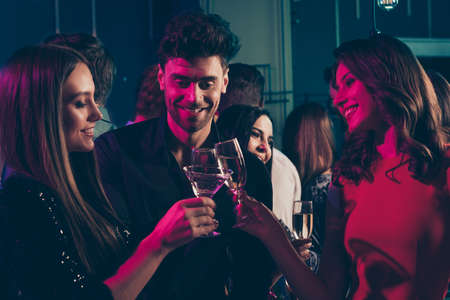 Photo portrait of trio of students drinking champagne together at nightclub in neon lights