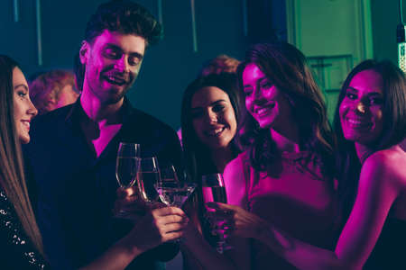 Photo portrait of students drinking champagne together clinking glasses in neon light