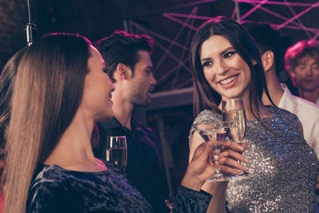 Photo portrait of two girls clinking together champagne glasses at luxury nightclub wearing beautiful shiny dresses