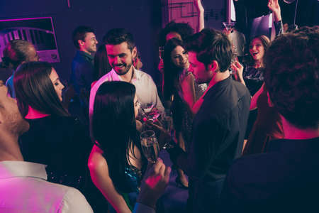 Photo portrait of people drinking champagne together at posh nightclub in neon lights