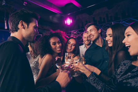 Photo portrait of guys and girls together clinking champagne and cocktail glasses at prom party