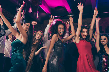 Photo portrait of wild crowd dancing together with hands in air at nightclub wearing beautiful formal dresses