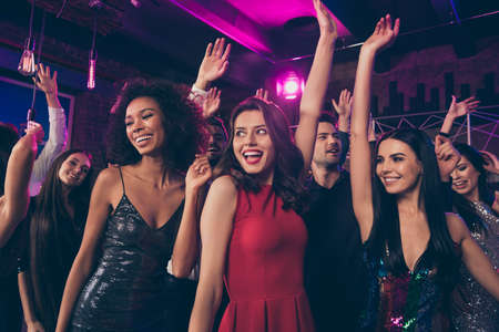 Photo portrait of excited young people dancing together at nightclub ladies wearing beautiful red shiny fancy elegant dresses Stok Fotoğraf