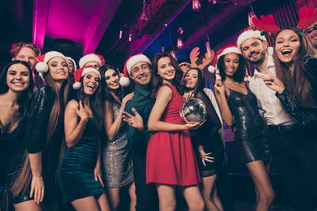 Photo portrait of friends posing together celebrating new year holding disco ball wearing silly dear headwear and santa hats Stok Fotoğraf