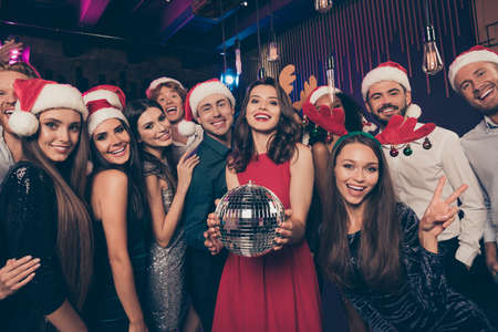 Photo portrait of excited people together holding disco ball wearing goofy christmas headwear welcoming new year