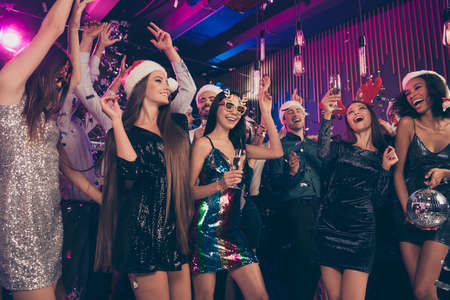 Photo portrait of cheerful people together dancing drinking alcohol holding disco ball wearing new year caps celebrating at posh nightclub with confetti