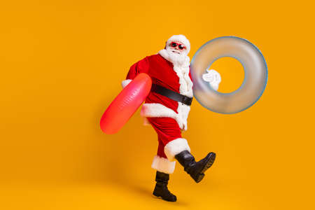 Full size profile side photo of white grey hair bearded santa claus rest x-mas christmas time go hold rubber circle wear sunglass headwear boots isolated bright shine color background