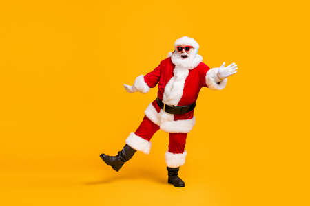 Full length photo of crazy santa claus with grey beard listen jolly holly music headset dance x-mas christmas party wear sunglass cap isolated bright shine color background Stockfoto